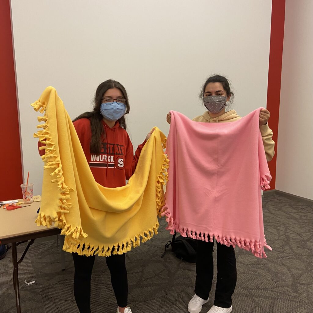Students show their blankets made for a service event called Project Linus in March 2021.
