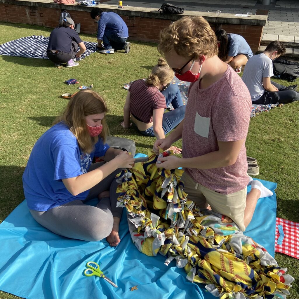 Students work on blankets in support of the Triangle Women's Center at a service event in April 2021.